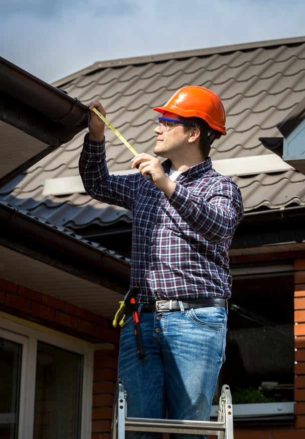 Young handyman standing on high ladder and measuring roof with tape